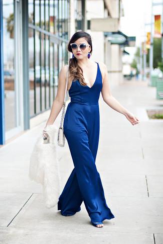 Wie kombinieren: weiße Pelzjacke, blauer Jumpsuit, blaue Satin Sandaletten, weiße gesteppte Leder Umhängetasche