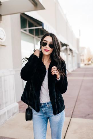 Wie kombinieren: schwarze Pelzjacke, graues Langarmshirt, hellblaue enge Jeans, schwarze gesteppte Leder Umhängetasche