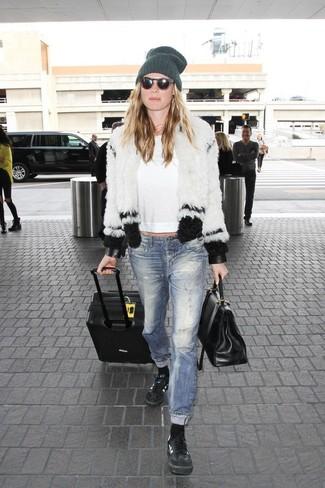 Wie kombinieren: weiße und schwarze Pelzjacke, weißes Langarmshirt, blaue Jeans mit Destroyed-Effekten, schwarze Leder niedrige Sneakers