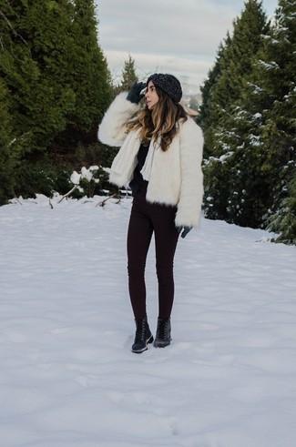 Wie kombinieren: weiße Pelzjacke, schwarzer flauschiger Pullover mit einem Rundhalsausschnitt, dunkellila enge Jeans, schwarze flache Stiefel mit einer Schnürung aus Leder