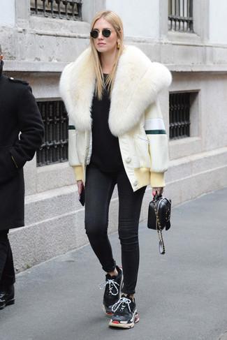Wie kombinieren: weiße Pelzjacke, schwarzer Pullover mit einem Rundhalsausschnitt, schwarze enge Jeans, schwarze Sportschuhe