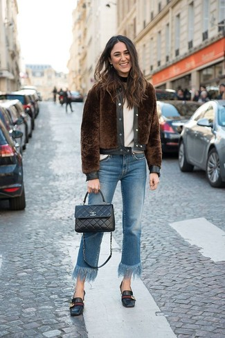 Wie kombinieren: braune Pelzjacke, weißer Pullover mit einem Rundhalsausschnitt, blaue Jeans mit Fransen, schwarze Leder Slipper