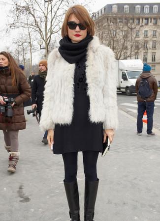 Wie kombinieren: weiße Pelzjacke, schwarzer Pullover mit einem Rundhalsausschnitt mit Blumenmuster, schwarzer Wollminirock, schwarze kniehohe Stiefel aus Leder