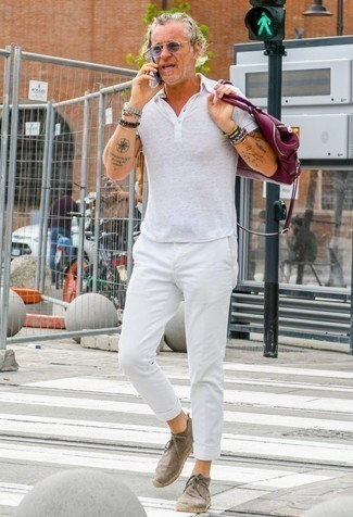60 Jährige: Silberne Uhr kombinieren – 37 Herren Outfits: Erwägen Sie das Tragen von einem weißen Polohemd und einer silbernen Uhr für einen entspannten Wochenend-Look. Komplettieren Sie Ihr Outfit mit braunen Chukka-Stiefeln aus Wildleder, um Ihr Modebewusstsein zu zeigen.