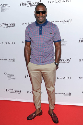 Idris Elba trägt Lila Polohemd mit Karomuster, Hellbeige Chinohose, Dunkelrote Leder Slipper, Schwarze Lederuhr