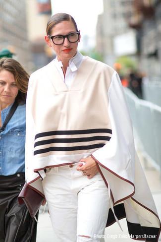 Jenna Lyons trägt hellbeige Poncho, weißes Businesshemd, weiße Jeans mit Destroyed-Effekten, dunkelrote Leder Clutch