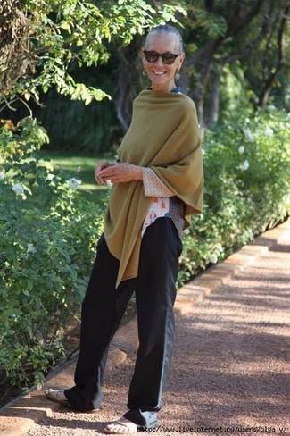 Wie kombinieren: olivgrüner Poncho, weißes bedrucktes Langarmshirt, schwarze weite Hose, hellbeige flache Sandalen aus Leder