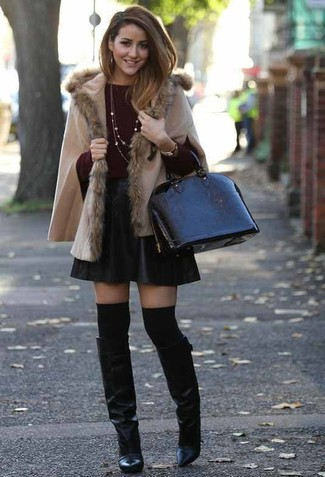 Wie kombinieren: hellbeige Poncho, dunkelroter Pullover mit einem Rundhalsausschnitt, schwarzer Skaterrock aus Leder, schwarze kniehohe Stiefel aus Leder