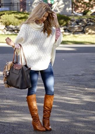 Wie kombinieren: weißer Strick Poncho, roter und weißer horizontal gestreifter Rollkragenpullover, blaue enge Jeans, beige kniehohe Stiefel aus Leder