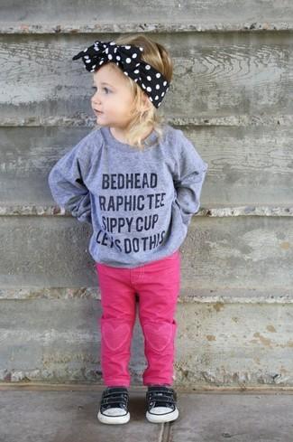 Wie kombinieren: grauer bedruckter Pullover, fuchsia Jeans, schwarze Turnschuhe, schwarzes Haarband
