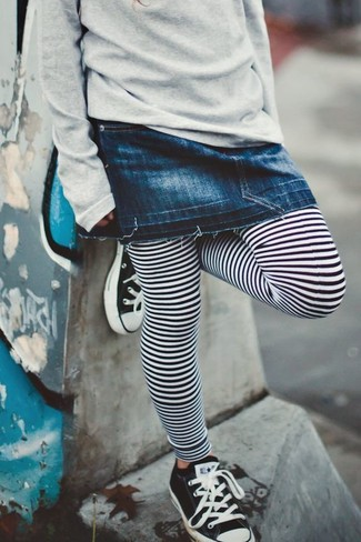 Wie kombinieren: grauer Pullover, dunkelblauer Jeansrock, weiße und schwarze horizontal gestreifte Leggings, schwarze und weiße Turnschuhe