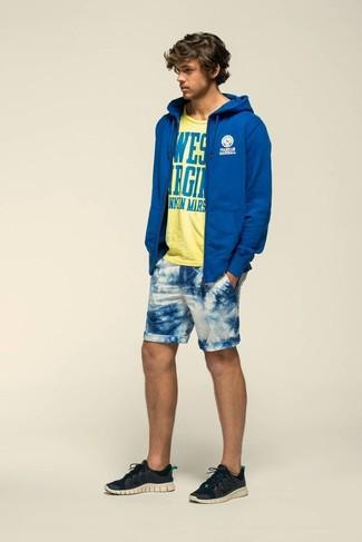 Wie kombinieren: blauer Pullover mit einem Kapuze, gelbes bedrucktes T-Shirt mit einem Rundhalsausschnitt, weiße und blaue bedruckte Shorts, schwarze Sportschuhe