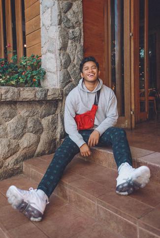 Wie kombinieren: grauer Pullover mit einem Kapuze, dunkelgrüne Chinohose mit Schottenmuster, weiße Sportschuhe, rote und schwarze Bauchtasche