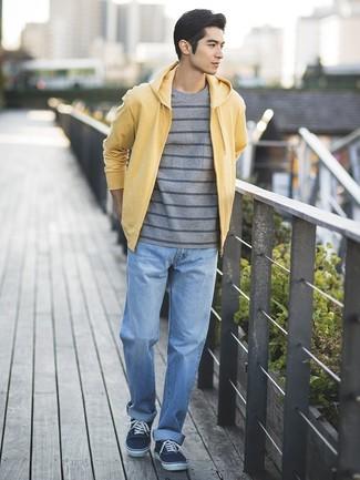 Wie kombinieren: gelber Pullover mit einem Kapuze, graues horizontal gestreiftes T-Shirt mit einem Rundhalsausschnitt, hellblaue Jeans, dunkelblaue Segeltuch niedrige Sneakers