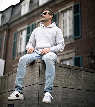 Wie kombinieren: grauer Pullover mit einem Kapuze, hellblaue Jeans mit Destroyed-Effekten, weiße bedruckte Leder niedrige Sneakers, schwarze Sonnenbrille