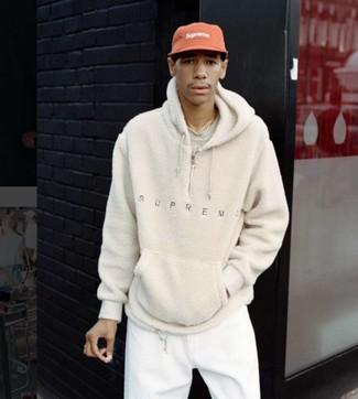 Wie kombinieren: hellbeige Fleece-Pullover mit einem Kapuze, hellbeige T-Shirt mit einem Rundhalsausschnitt, weiße Jogginghose, rote Baseballkappe