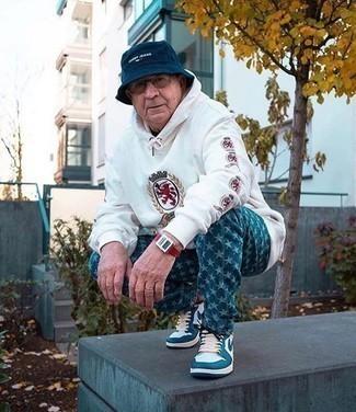 Blaue bedruckte Jeans kombinieren – 12 Herren Outfits: Kombinieren Sie einen weißen bedruckten Pullover mit einem Kapuze mit blauen bedruckten Jeans für einen entspannten Wochenend-Look. Vervollständigen Sie Ihr Look mit weißen und blauen hohen Sneakers aus Leder.