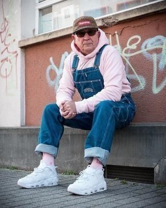Herren Outfits 2020: Entscheiden Sie sich für Komfort in einem rosa Pullover mit einem Kapuze und einer blauen Jeans Latzhose. Ergänzen Sie Ihr Look mit weißen Sportschuhen.