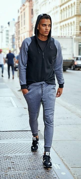 Wie kombinieren: schwarzer Pullover mit einem Kapuze, schwarzes T-Shirt mit einem Rundhalsausschnitt, graue Jogginghose, schwarze Sportschuhe