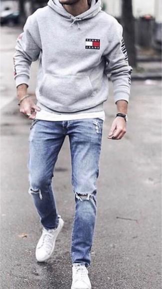 Wie kombinieren: grauer Pullover mit einem Kapuze, weißes T-Shirt mit einem Rundhalsausschnitt, blaue enge Jeans mit Destroyed-Effekten, weiße Segeltuch niedrige Sneakers