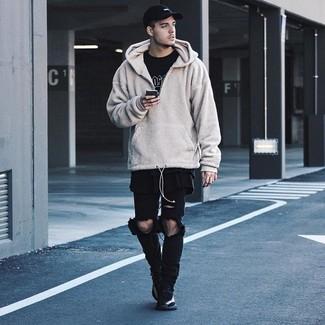 Wie kombinieren: hellbeige Fleece-Pullover mit einem Kapuze, schwarzes und weißes bedrucktes T-Shirt mit einem Rundhalsausschnitt, schwarze Jeans mit Destroyed-Effekten, schwarze Sportschuhe