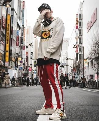 Wie kombinieren: hellbeige bedruckter Pullover mit einem Kapuze, schwarzes T-Shirt mit einem Rundhalsausschnitt, rote und weiße vertikal gestreifte Jogginghose, hellbeige Leder Sportschuhe