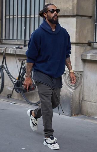 Dunkelgraue Jogginghose kombinieren: trends 2020: Für ein bequemes Couch-Outfit, vereinigen Sie einen dunkelblauen Pullover mit einem Kapuze mit einer dunkelgrauen Jogginghose. Vervollständigen Sie Ihr Look mit weißen und dunkelblauen Sportschuhen.