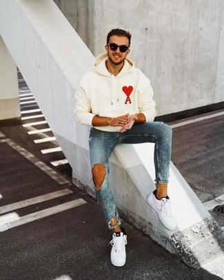 Wie kombinieren: weißer bedruckter Pullover mit einem Kapuze, blaue enge Jeans mit Destroyed-Effekten, weiße und schwarze Leder niedrige Sneakers, schwarze Sonnenbrille