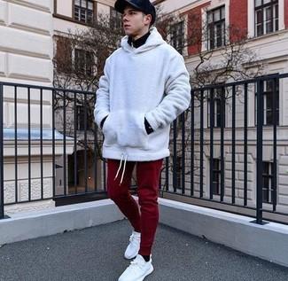 Wie kombinieren: schwarzer Pullover mit einem Reißverschluss am Kragen, weißer Pullover mit einem Kapuze, dunkelrote Jogginghose, weiße Segeltuch niedrige Sneakers
