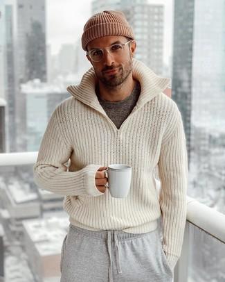 Wie kombinieren: hellbeige Strick Pullover mit einem Reißverschluß, dunkelgraues T-Shirt mit einem Rundhalsausschnitt, graue Jogginghose, braune Mütze
