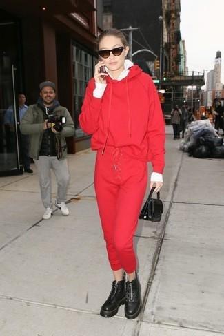 Wie kombinieren: weißer Pullover mit einem Reißverschluß, roter Pullover mit einer Kapuze, rote Jogginghose, schwarze klobige flache Stiefel mit einer Schnürung aus Leder