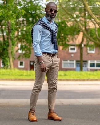 Wie kombinieren: dunkelblauer horizontal gestreifter Pullover mit einem Rundhalsausschnitt, hellblaues Businesshemd, beige Chinohose, rotbraune Leder Oxford Schuhe