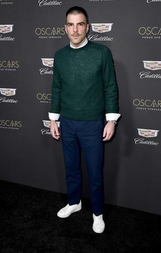 Wie kombinieren: dunkelgrüner Pullover mit einem Rundhalsausschnitt, weißes Businesshemd, dunkelblaue Chinohose, weiße niedrige Sneakers