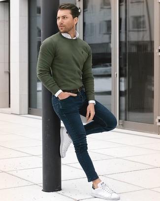 Wie kombinieren: olivgrüner Pullover mit einem Rundhalsausschnitt, weißes Businesshemd, dunkelblaue enge Jeans, weiße Leder niedrige Sneakers