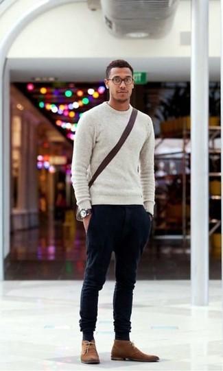 Wie kombinieren: grauer Pullover mit einem Rundhalsausschnitt, schwarze Chinohose, braune Chukka-Stiefel aus Wildleder, dunkelbraune Segeltuch Umhängetasche