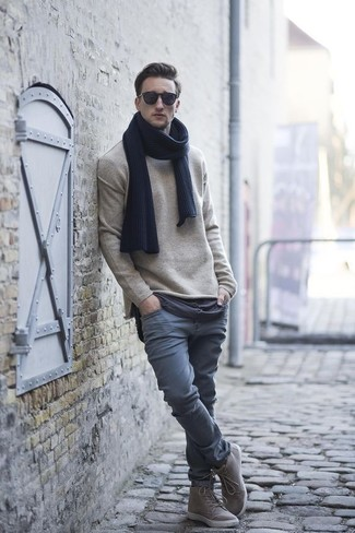 Wie kombinieren: hellbeige Pullover mit einem Rundhalsausschnitt, graue Chinohose, graue hohe Sneakers, dunkelblauer Schal