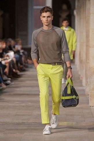 Wie kombinieren: brauner Pullover mit einem Rundhalsausschnitt, gelbe Chinohose, graue Segeltuch niedrige Sneakers, dunkelblaue Segeltuch Sporttasche