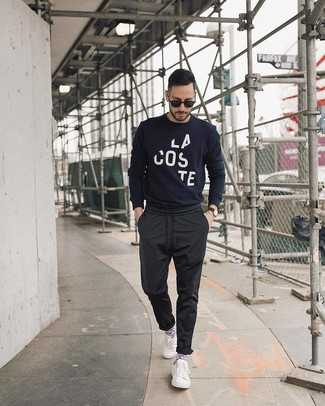 Wie kombinieren: dunkelblauer und weißer bedruckter Pullover mit einem Rundhalsausschnitt, schwarze Chinohose, weiße niedrige Sneakers, schwarze Sonnenbrille