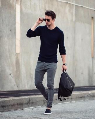 Wie kombinieren: dunkelblauer Pullover mit einem Rundhalsausschnitt, graue Jeans, schwarze Slip-On Sneakers, schwarzer Rucksack