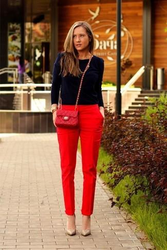 Wie kombinieren: dunkelblauer Pullover mit einem Rundhalsausschnitt, rote Karottenhose, beige Leder Pumps, rote gesteppte Leder Umhängetasche