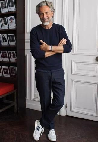 Weiße niedrige Sneakers kombinieren: trends 2020: Paaren Sie einen schwarzen Pullover mit einem Rundhalsausschnitt mit einer schwarzen Chinohose für einen bequemen Alltags-Look. Weiße niedrige Sneakers verleihen einem klassischen Look eine neue Dimension.