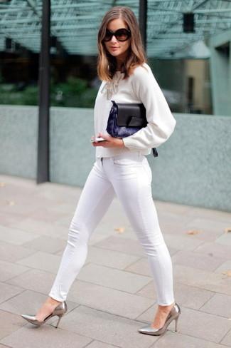 Wie kombinieren: weißer Pullover mit einem Rundhalsausschnitt, weiße enge Jeans, silberne Leder Pumps, dunkelblaue Pelz Clutch