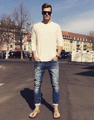 Wie kombinieren: hellbeige Pullover mit einem Rundhalsausschnitt, dunkelblaue enge Jeans mit Destroyed-Effekten, hellbeige Wildledersandalen, schwarze Sonnenbrille
