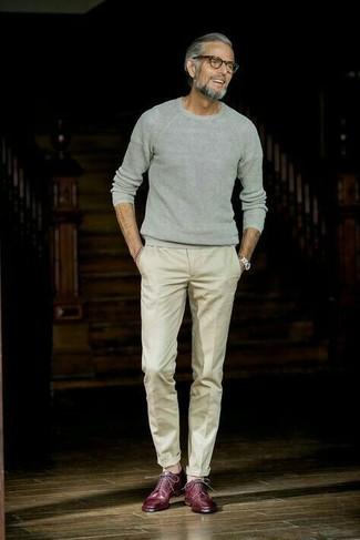 Wie kombinieren: grauer Pullover mit einem Rundhalsausschnitt, hellbeige Anzughose, dunkelrote Leder Derby Schuhe, silberne Uhr