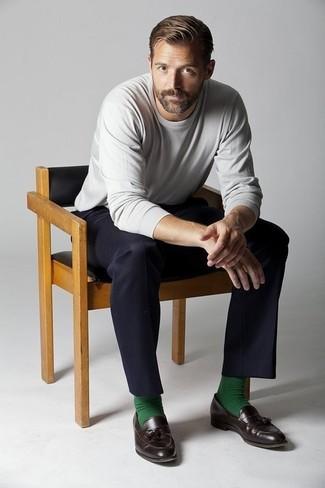Wie kombinieren: grauer Pullover mit einem Rundhalsausschnitt, schwarze Anzughose, dunkelbraune Leder Slipper mit Quasten, grüne Socke