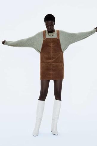 Wie kombinieren: grauer Pullover mit einem Rundhalsausschnitt, brauner Wildleder Kleiderrock, weiße kniehohe Stiefel aus Leder, goldene Halskette
