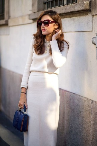 Wie kombinieren: hellbeige Pullover mit einem Rundhalsausschnitt, hellbeige Midirock, dunkelblaue Leder Clutch mit Schlangenmuster, dunkelrote Sonnenbrille