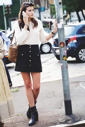 Probieren Sie die Kombi aus einem hellbeige Pullover mit einem Rundhalsausschnitt und einem schwarzen Rock mit Knöpfen, umein lockeres Outfit zu kreieren, der in der Garderobe der Frau auf keinen Fall fehlen darf. Schwarze leder stiefeletten fügen sich nahtlos in einer Vielzahl von Outfits ein.