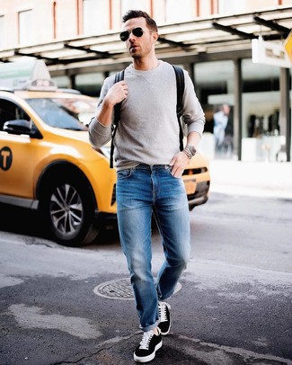 Wie kombinieren: grauer Pullover mit einem Rundhalsausschnitt, blaue Jeans, schwarze niedrige Sneakers, schwarzer Leder Rucksack