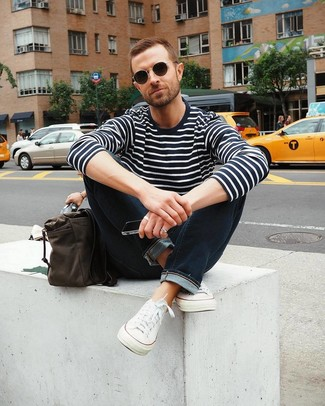 Wie kombinieren: dunkelblauer und weißer horizontal gestreifter Pullover mit einem Rundhalsausschnitt, dunkelblaue Jeans, weiße Segeltuch niedrige Sneakers, dunkelbraune Leder Umhängetasche